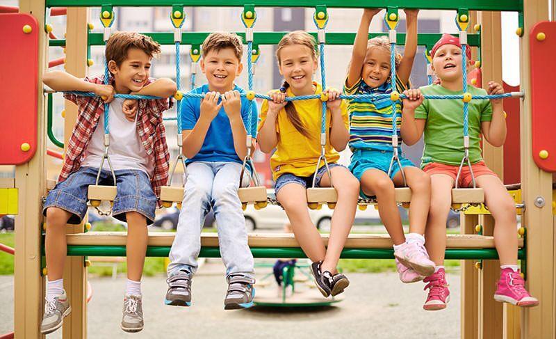 Kinder sitzen auf einem Klettergerüst
